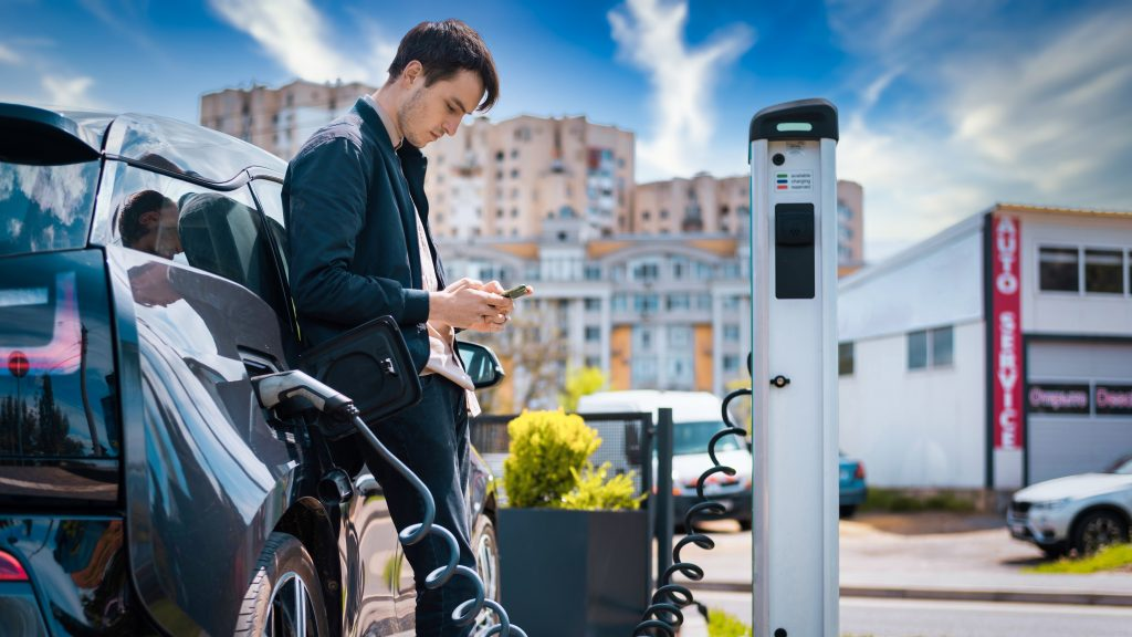 man charging his electric car charge station using smartphone