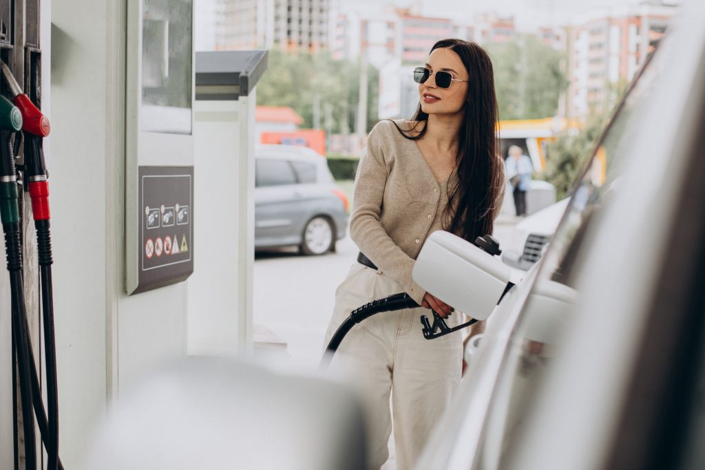 young woman fueling her car